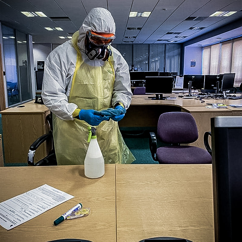 Operator decontaminating office desk