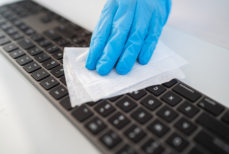 Keyboard being wiped with sanitiser