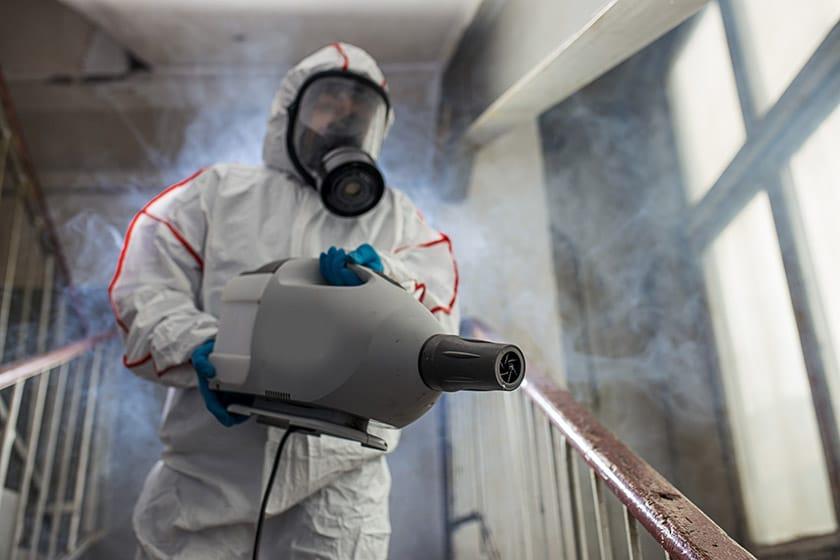 Cleaner in hazmat suit using fogging machine