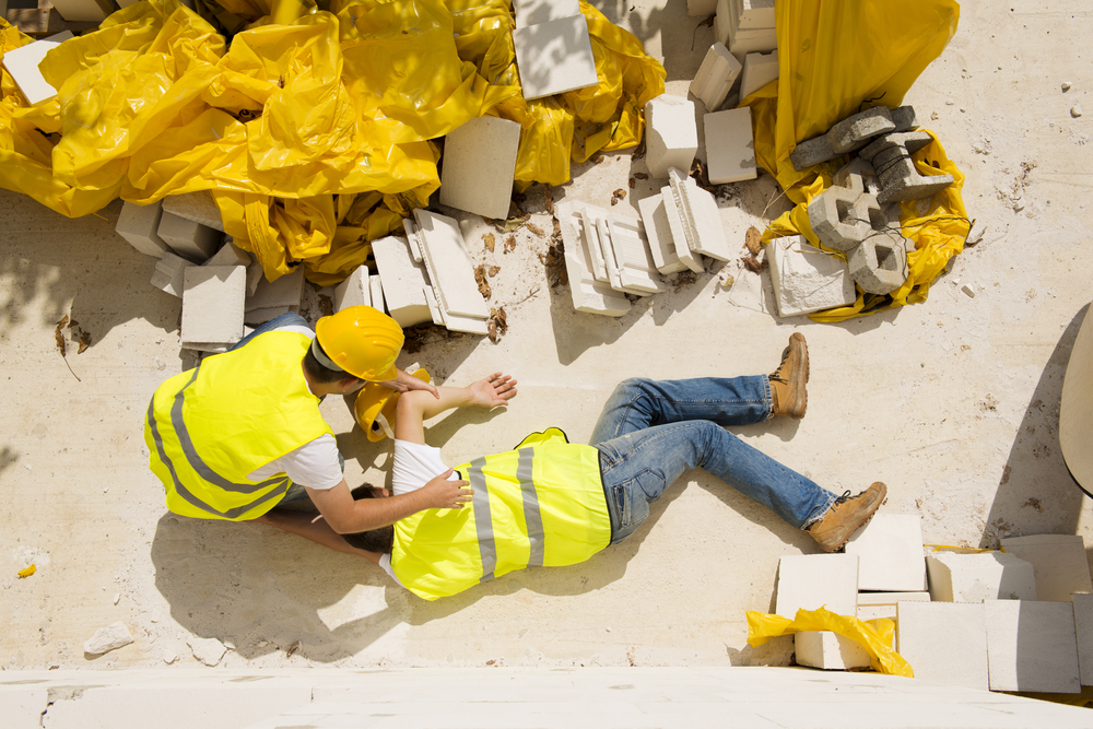A man lays on the ground after falling from height at work