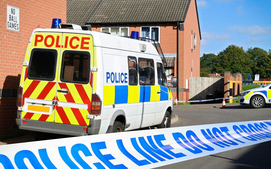 Crime scene cordon tape in front of police van