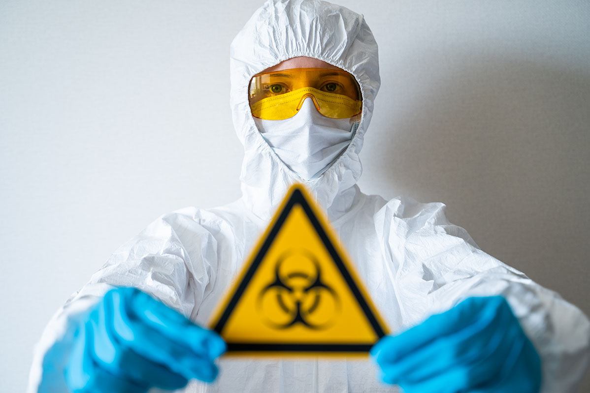 A person wearing full PPE holds a biohazard sign