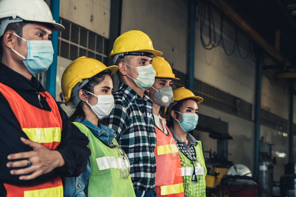 Five workers stand in line wearing PPE