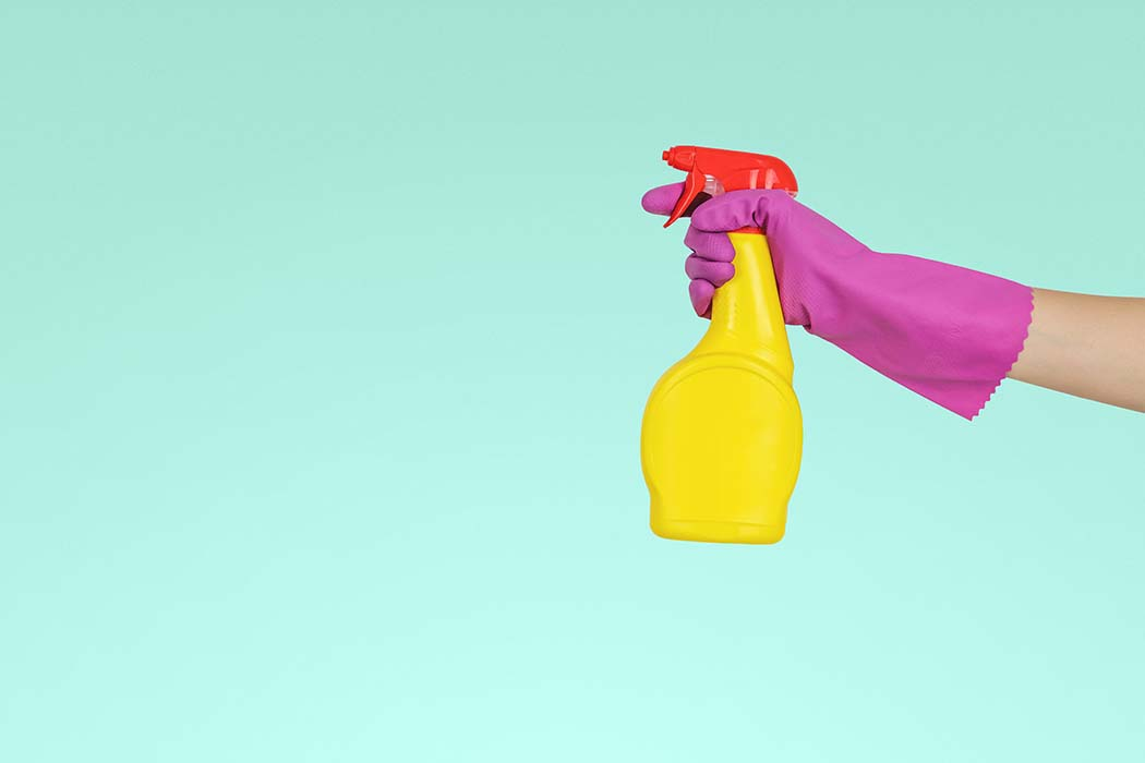 a gloved hand holding a spray bottle of cleaning product