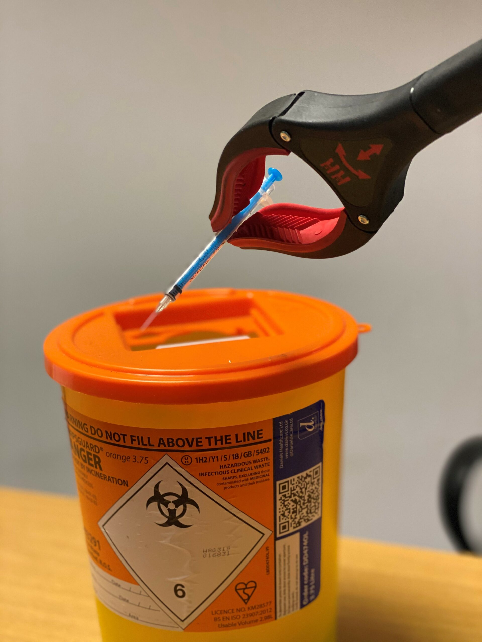 A needle is placed into a sharps container using a needle picker